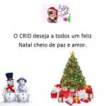 cão com chapéu de natal. A preto O CRID deseja a todos um feliz natal cheio de paz e amor. No canto inferior direito dois bonecos de neve e do lado direito uma árvore de natal enfeitada e rodeada por presentes