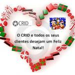 Coração feito de presentes. Do lado esquerdo o logógito do CRID, no direito o Mickey e Pato donald com flocos de neve a cair do céu e a preto o crid e todos os seus clientes desejam um feliz natal.