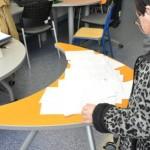 jovem de costas olha para mesa com vários desenhos