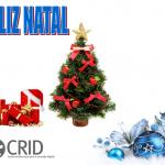 Feliz Natal a azul com contorno vermelho. Presentes embrulhados no canto inferior esquerdo e o logótipo do CRID. No meio uma árvore de natal enfeitada com laços vermelhos e no canto inferior direito bolas azuis de natal.