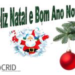 A verde Feliz natal e bom ano novo. Um pai natal de braços abertos e ao lado uma bola pendurada num ramo da árvore.No canto inferior esquerdo o logótipo do CRID