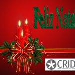 Feliz Natal a verde, arranjo com duas velas vermelhas, azevinho e um laço vermelho e dourado. No canto inferior direito o logótipo do CRID