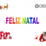 Feliz Natal centrado e em letras coloridas. Uma rena, o logótipo do CRID, um gato dentro de um barrete de natal e presentes embrulhados, um em cada canto.