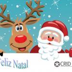 Uma rena sorridente ao lado do pai natal com céu azul estrelado. No canto inferior Feliz Natal e o logótipo do CRID,