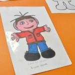 Desenho de um menino moreno, de braços abertos com camisola vermelha, calças azuis e sapatos pretos.